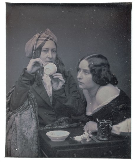 Woman holding teacup sideways sitting next to younger women who peers in
