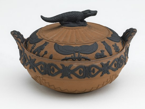 A terra cotta bowl with a black crocodile on top. There are handles and a black decorative design around the edges of the pot, with animals and ankhs