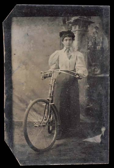 Black and white photograph of a woman posing, unsmiling, with a bicycle