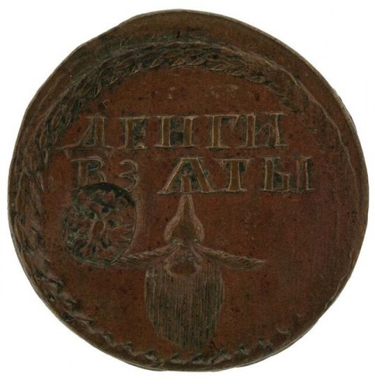 A rust-colored coin with two lines of text, a frond around the edge and a depiction of a nose, whiskers and beard