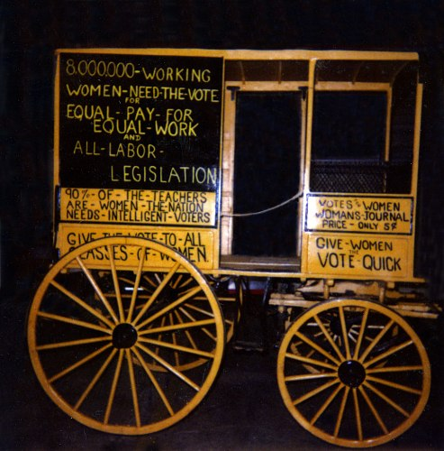 "A yellow wooden wagon with four wheels: two large wheels on the left and two smaller ones on the right. The wagon is adorned with slogans for woman's suffrage such as ""equal pay for equal work and all labor legislation."""