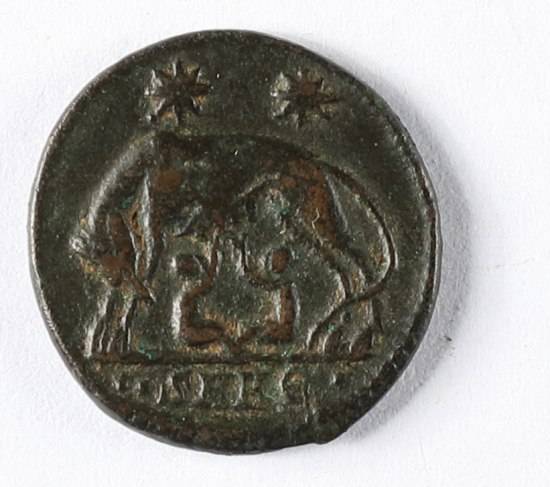 A dark metal coin. There are two starbursts over an animal in the middle with two small humans underneath it.