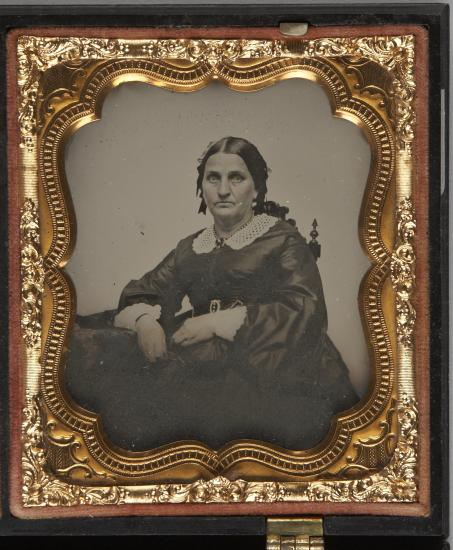 Black and white photo of woman in fancy gold frame. Her hair is parted down the middle. White collar and black dress. Serious expression.