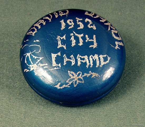 """A photo looking down at a blue wooden yo-yo from the top. Someone has roughly scratched """"David Jarol 1952 City Champ"""" on it."""