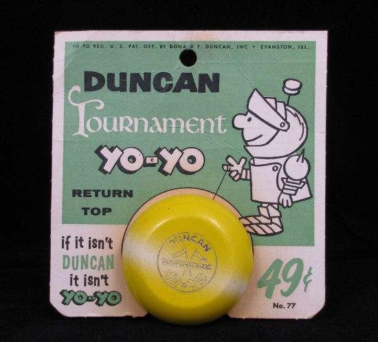 "Yellow yo-yo mounted on a display card featuring an image of the mascot ""Mr. Yo-Yo"" and the slogan ""If it isn't Duncan it isn't Yo-Yo."""