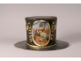 """This fire hat was used by a member of the United States Hose Company of Philadelphia, Pennsylvania during the early 19th century. The hat is painted black overall with an image of Lady Liberty holding a liberty pole with Phrygian cap on top and her arm over a United States shield that reads """"Liberty."""" The image is framed in an oval cartouche bordered in gold. There is a golden trimmed banner on either side of the central image that reads """"UNITED STATES"""" in gold. The back of the hat has a golden image of a f"""