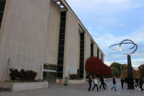 "Photo of the museum in fall, with red leaves and ""Infinity"" sculpture, as a group exits the building"