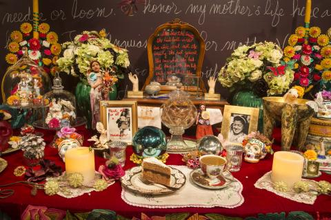 "A slice of cake and tea cup full of coffee with cream among flowers and other ""ofrenda"" items"