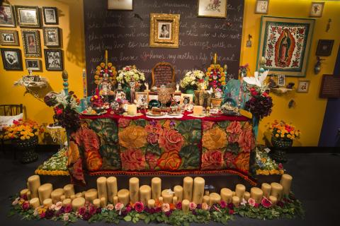 """A Room of Her Own"" by Sandra Cisneros at the National Museum of American History, featuring yellow walls, framed photos, flowers, candles, and more"