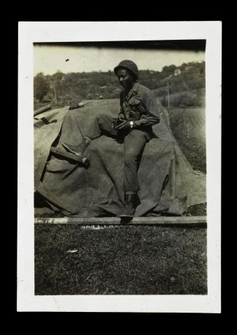 Paul Bland poses with his camera in front of a military tent