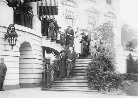 Group of people led by Dr. Marie Curie and President Harding walking down steps at the White House