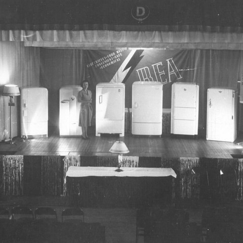 "(Zoom/Detail) Black and white photo of a woman on a stage. On stage are six fridges, two lamps, and a big banner that says ""REA."" On a table on the floor in front of the stage, a lamp. There are decorative tassels."