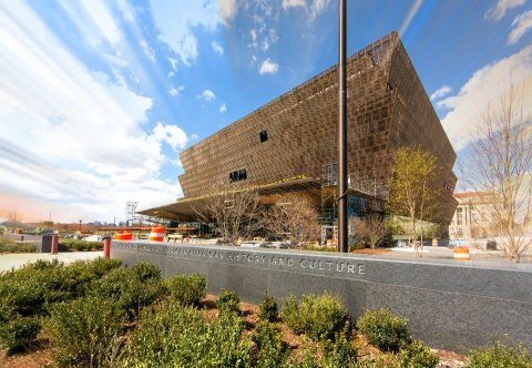 Color photograph of the National Museum of African American History and Culture, taken from ground level with a perspective looking up. Light and puffy clouds streak across the sky. Green foliage in foreground.