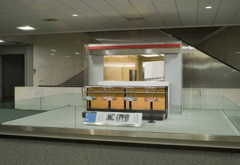 A photo from the museum of the installed portion of the counter from the Greensboro diner. It includes the countertop, four chairs, and part of the back wall with a mirror on it.