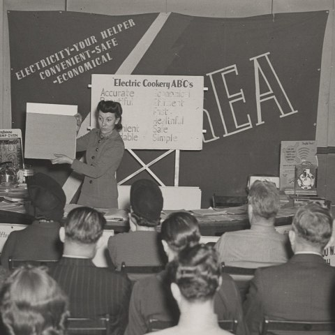 """A woman delivers a presentation in front of a large group of seated people. The stage is filled with various electrical appliances, as well as a large banner with the text, """"Electricity, your helper, convenient, safe, economical,"""" as well as as a smaller poster titled """"Electric Cooking ABCs."""""""