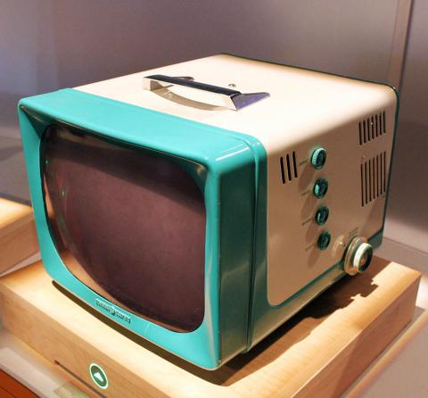 Small television with handle and turquoise frame around screen, which is slightly curved