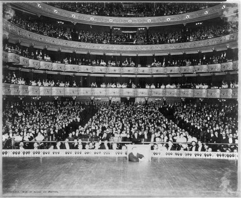 Image from stage showing multiple tiers of audience packed into the seats