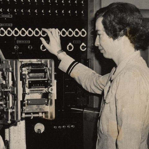 Grace Hopper examines a computer at work.