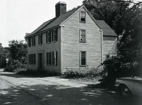 Black and white photo of a two-story house. Part of a car is visible in the foreground.