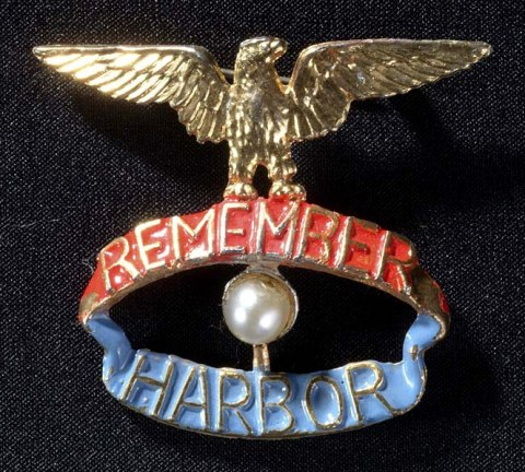 """A pin, presumably for a woman. There is a gold eagle perched on top with its wings outstretched. It stands on top of a red banner saying """"Remember"""" which is over a blue banner that says """"Harbor"""" Between the banners is a pearl."""