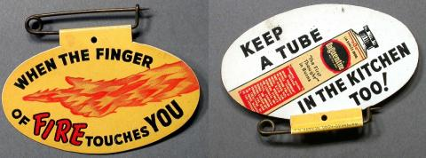 Celluloid pin featuring fire and a tube of burn salve