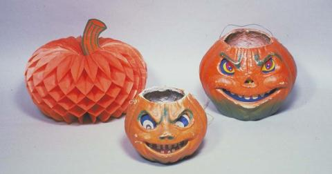 A paper pumpkin decoration and two evil jack 'o lanterns