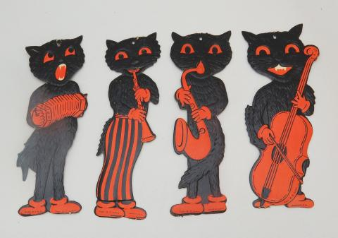 Four black cat decorations (flat) with orange details. One is playing accordion. Because cats know how to do that?