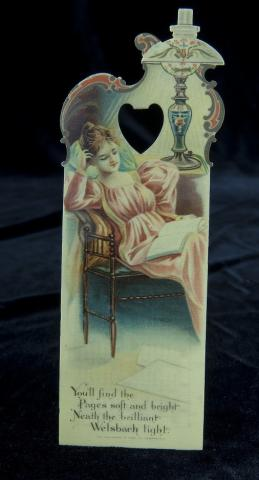 Celluloid bookmark featuring a lady reading under a lamp