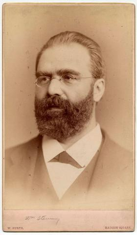 Black-and-white photograph of a bearded man with glasses