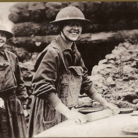 """This 1918 photo from the National Archives shows a cheerful American Salvation Army """"lassy"""" rolling pie crusts for men of the 26th Division in France."""