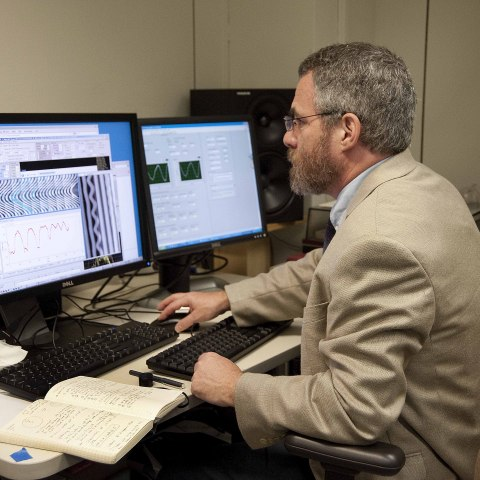 A man sits in front of several monitors, studying them