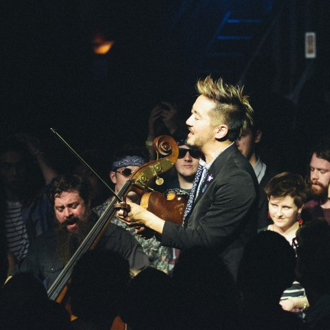Musicians playing string instruments in a dark room surrounded by onlookers