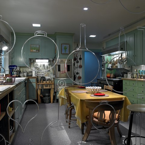 A view through glass etched with pots and pans of a kitchen with table, cupboards, stove and ovens
