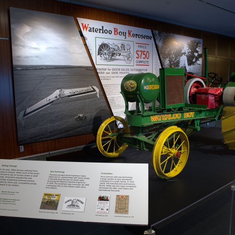 A bright green and yellow machine with spindled wheels rests in front of three large graphic panels. There is a short plastic barrier in the foreground and a grey rectangular display with type and pictures.