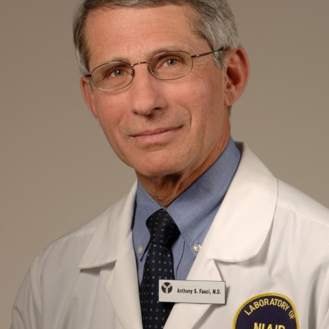 A grey-haired man in a lab coat looks at the camera with a faint smile in a formal portrait