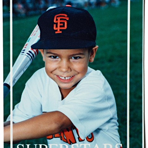 A baseball card depicting a young, smiling boy in a uniform brandishing a baseball bat
