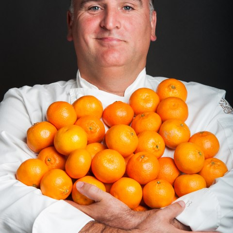 A man in a white chefs coat stands holding an armful of oranges