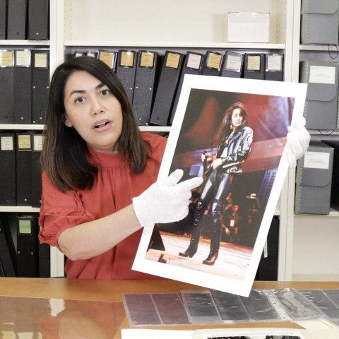 Curator pointing to printed photograph of Selena