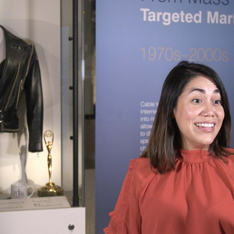 Curator taking photo in front of leather jacket