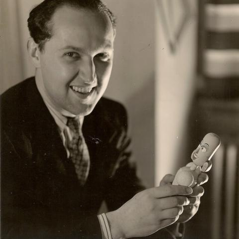 Black and white portrait of George Pal, holding puppet