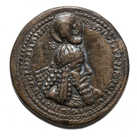 One side of a bronze coin, showing a man with a helmet and a bounty of hair and an altar-like structure with text and votives on the reverse