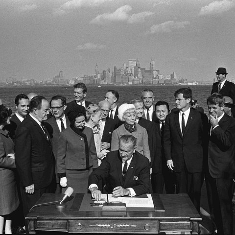 President Johnson sits at a desk outdoors with a view of the New York coastline in the background. Many people gather around him watching. American flag on pole beside desk.