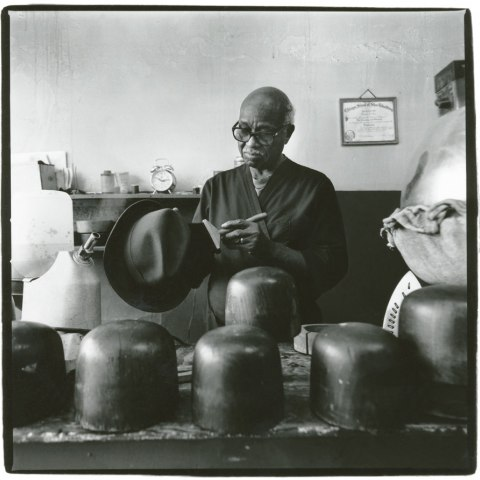Picture of Harold Cotton, Hat Blocker by Harvey Wang. Harold Cotton cleans a fedora with a brush. A group of hat blocks sit in the foreground, and Cotton's diploma hangs on the wall behind him.