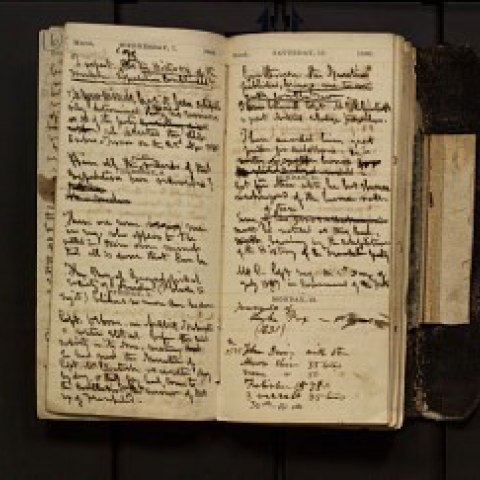 A journal with yellowed pages and dark cursive script laying open. There is a small sandbag next to it.