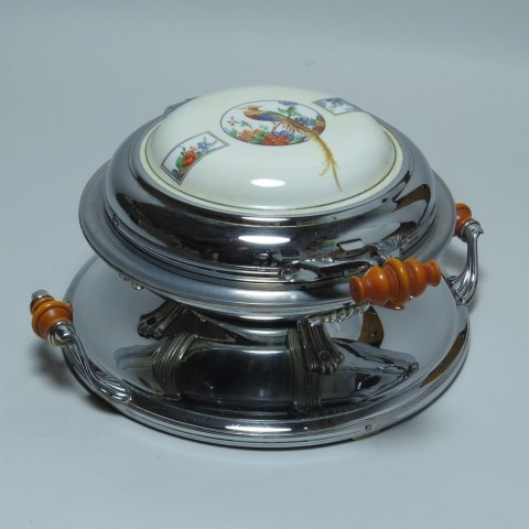 A shiny metal object with a round base and small wooden handles. There is an object resembling a covered bowl with white material inlaid bearing an illustration