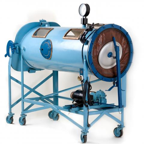 Large tube-shaped machine with six legs on rolling wheels. Blue in color with small windows.