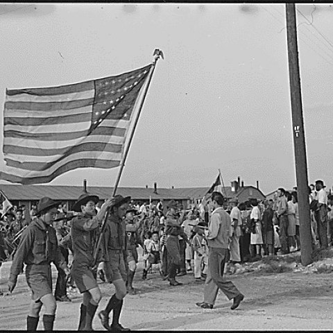 Black and white photo of three Boy Scouts carrying a large U.S. flag with community in background, including other parade participants with bugle and drum.