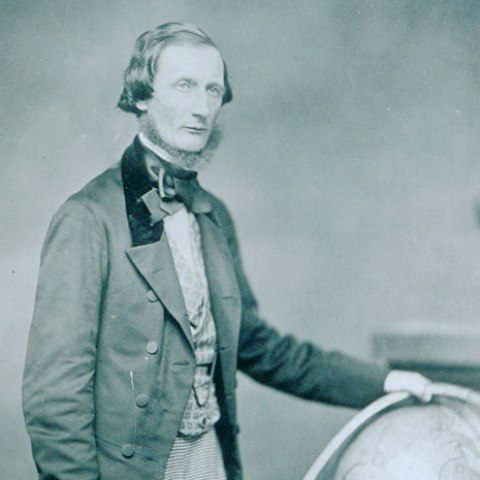 A photograph of a man in the garb of the 1860s. He rests his hand on a large globe on the ground as he stands and looks at something out of the right side of the frame. In his right hand he carries a rolled up paper.