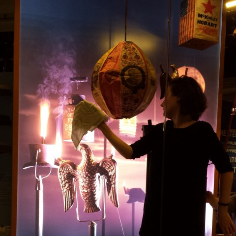 A woman stands inside a case with metal objects attached to poles, and there are lanterns hung up. She holds a white cloth out and attempts to clean the glass in front of her.