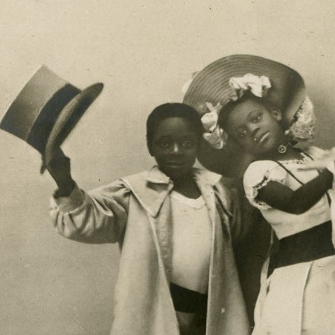 Detail: Postcard with photo of two young children wearing ballet shoes. Little boy holds top hat in his raised hand and an over-sized coat. The little girl strikes a pose with a fancy fan and wears a full-skirted tea length dress and a hat with many bows.